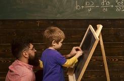 Studente di vista laterale ed insegnante davanti alla lavagna Bambino di aiuto dell'istitutore o del padre per scrivere le letter fotografia stock