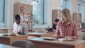 Studente die met boek en tablet werken stock footage