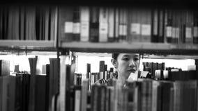 Studente die tussen planken lopen, die naar boeken zoeken