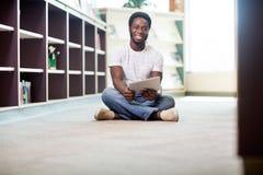Studente With Digital Tablet che si siede nella biblioteca Fotografia Stock Libera da Diritti