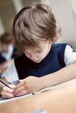 Studente diligente che si siede allo scrittorio, aula Fotografia Stock Libera da Diritti