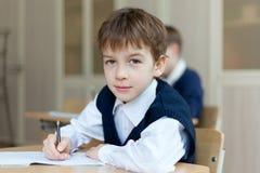 Studente diligente che si siede allo scrittorio, aula Fotografie Stock