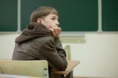 Studente diligente che si siede allo scrittorio, aula Fotografie Stock Libere da Diritti