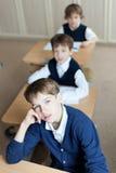 Studente diligente che si siede allo scrittorio, aula Fotografia Stock