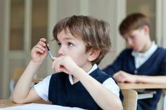 Studente diligente che si siede allo scrittorio, aula Immagini Stock