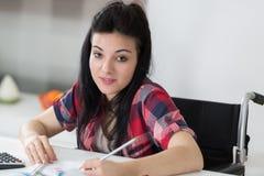 Studente disattivato sorridente in biblioteca all'università Immagine Stock Libera da Diritti