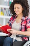 Studente disattivato sorridente in libro di lettura delle biblioteche all'università Fotografia Stock Libera da Diritti