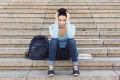 Studente disperato che si siede sulle scale all'aperto Fotografia Stock