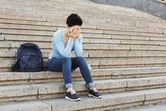 Studente disperato che si siede sulle scale all'aperto Immagini Stock