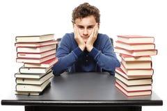 Studente disperato con il fronte in mani che si siedono al suo scrittorio in mezzo Immagini Stock