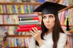 Studente divertente con i libri della tenuta del cappuccio di graduazione Immagini Stock