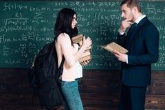Studente e professore di vista laterale che hanno una discussione Ragazza con lo zaino ed il mucchio pesanti dei libri nel suo st fotografia stock