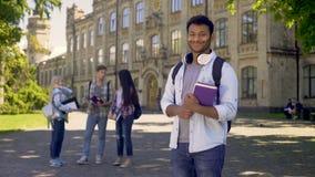 Studente eccellente che sta vicino alla sua università, sorridente francamente alla macchina fotografica video d archivio