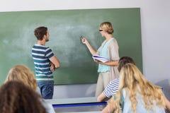 Studente ed insegnante che indicano alla lavagna nella classe Fotografie Stock Libere da Diritti