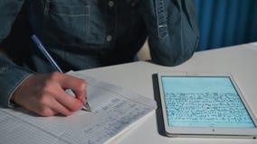 Studente In een jeansoverhemd die het werk doen die een tablet gebruiken Close-up stock footage