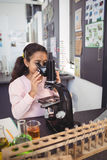 Studente elementare che esamina tramite il microscopio il laboratorio Fotografie Stock Libere da Diritti