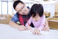 Studente elementare che studia con il suo insegnante Fotografia Stock Libera da Diritti