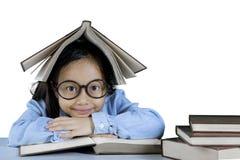 Studente elementare con un libro sopra la sua testa Immagini Stock Libere da Diritti