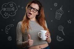 Studente emozionale che mette il suo pollice su mentre bevendo caffè Fotografia Stock