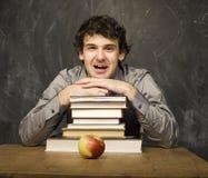studente emozionale con i libri e mela rossa nella stanza di classe, alla lavagna Immagine Stock Libera da Diritti