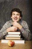 Studente emozionale con i libri e mela rossa nella stanza di classe, alla lavagna Immagini Stock