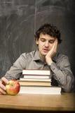 Studente emozionale con i libri e mela rossa nella stanza di classe, alla lavagna Immagini Stock Libere da Diritti