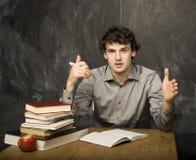 Studente emozionale con i libri e mela rossa nella stanza di classe, alla lavagna Immagine Stock