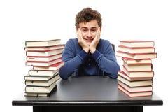 Studente enorme con il fronte in mani che si siedono al suo betwe dello scrittorio Immagine Stock