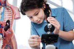 Studente entusiasta messo a fuoco che ripara un microscopio Fotografia Stock