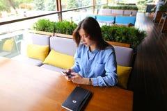 Studente europeo femminile che si siede al caffè con il taccuino sulla tavola e che per mezzo dello smartphone Immagine Stock Libera da Diritti