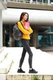 Studente felice che cammina per classificare con la borsa ed i libri Fotografie Stock