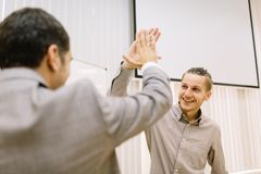 Studente felice che dà un alto--cinque ad un professore su un fondo vago Sfera differente 3d Fotografia Stock Libera da Diritti