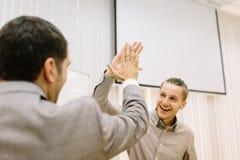 Studente felice che dà un alto--cinque ad un professore su un fondo vago Sfera differente 3d Immagini Stock Libere da Diritti