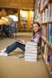 Studente felice che per mezzo del computer portatile sul pavimento delle biblioteche che esamina computer portatile Immagine Stock Libera da Diritti