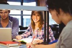 Studente felice che si siede alla scrittura dello scrittorio che sorride alla macchina fotografica Fotografie Stock