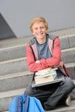 Studente felice che si siede con i libri ed il computer portatile Fotografie Stock