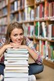 Studente felice che si siede sul pavimento delle biblioteche che si appoggia mucchio dei libri Immagini Stock Libere da Diritti
