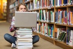 Studente felice che si siede sul pavimento delle biblioteche facendo uso del computer portatile sul mucchio dei libri Fotografia Stock Libera da Diritti