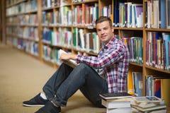 Studente felice che si siede sulla lettura del pavimento delle biblioteche Immagine Stock Libera da Diritti