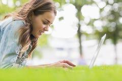 Studente felice che si trova sull'erba facendo uso del suo computer portatile Immagine Stock Libera da Diritti