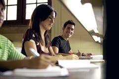 Studente felice che studia e che scrive Fotografia Stock