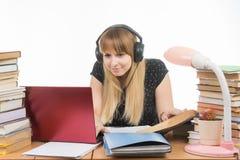 Studente felice con le cuffie che si siedono alla tavola e che cercano le informazioni che avete bisogno di in un computer portat Fotografie Stock
