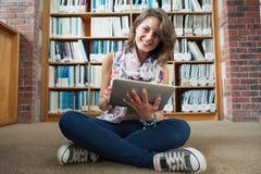Studente felice contro lo scaffale per libri con il PC della compressa sul pavimento delle biblioteche Fotografie Stock