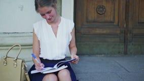 Studente felice di freshwoman della ragazza di istruzione superiore che si siede sui punti dell'università stock footage