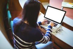 Studente felice nel corridoio di conferenza facendo uso del computer portatile Fotografia Stock