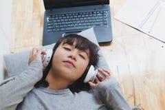 studente femminile dell'adolescente della ragazza asiatica che sta e che ascolta la musica Fotografie Stock Libere da Diritti
