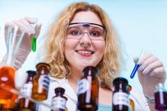 Studente femminile di chimica con la boccetta della prova della cristalleria Immagine Stock