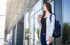 Studente femminile giovane dell'asiatico l'IT, con lo smartphone e zaino, caffè bevente prima della lezione e sorridere Fotografia Stock