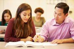 Studente femminile With Teacher Studying della High School allo scrittorio Fotografia Stock