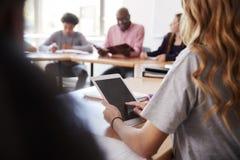 Studente femminile Using Digital Tablet della High School mentre sedendosi allo scrittorio nella classe fotografie stock libere da diritti